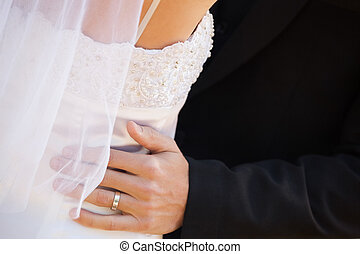 Mid section of newlywed couple embracing - Close-up mid...