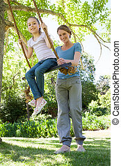 Happy mother swinging daughter at park - Low angle view of a...