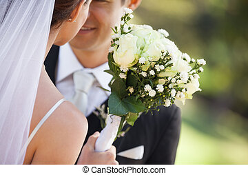 Mid section of a newlywed couple with bouquet in park -...
