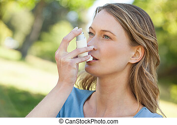 Woman using asthma inhaler in park - Close-up of a young...
