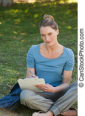 Relaxed young woman writing on clipboard at park - Portrait...