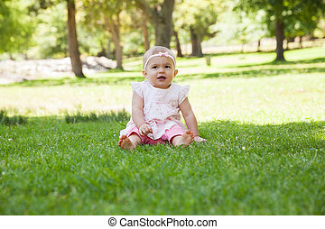 Happy cute baby sitting on grass at park - Full length of a...