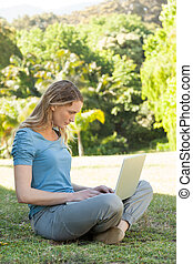 Relaxed young woman using laptop at