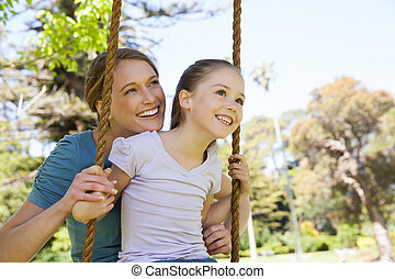 Happy mother swinging daughter at park - Close-up of a happy...