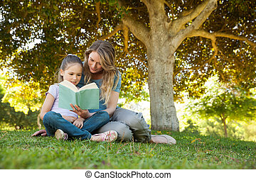 Mother and daughter reading a book at park - Full length of...