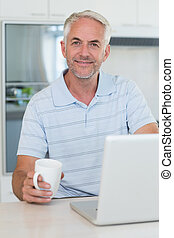 Casual smiling man using his laptop while having coffee at...