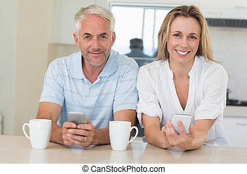 Happy couple sitting at the counter texting at home in the...