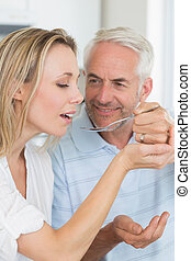 Happy man feeding his partner a spoon of the dinner at home...