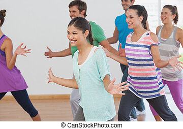 Cheerful fitness class and instructor doing pilates exercise...