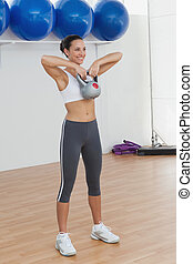 Full length of a fit woman exercising with kettlebell
