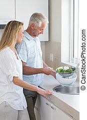 Couple rinsing vegetables at the sink at home in the kitchen