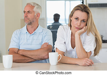 Fed up woman sitting at the counter with her partner at home...