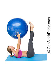 Side view of a fit woman exercising with fitness ball - Side...