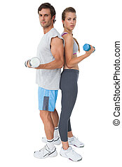 Portrait of a fit young couple exercising with dumbbell over...