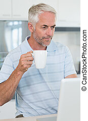 Casual man looking at his laptop while having coffee at home...