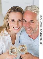 Happy couple having glass of wine together at home in the...