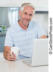 Casual man using his laptop while having coffee at home in...