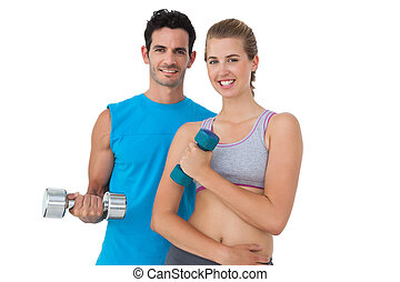 Portrait of a fit couple exercising with dumbbells -...
