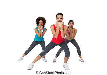 Full length portrait of women doing power fitness exercise...