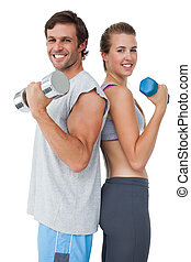 Portrait of a fit couple exercising with dumbbell - Portrait...