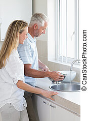 Couple rinsing vegetables in colander at home in the kitchen
