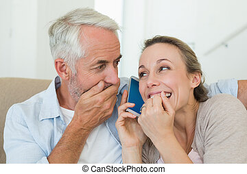 Happy couple listening to phone cal