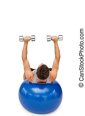 Young man exercising with dumbbells on fitness ball