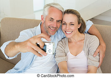 Happy couple taking a selfie together on the couch at home...