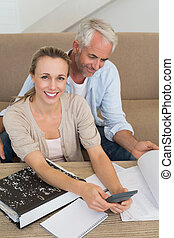 Smiling couple calculating their bills at the couch
