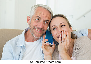 Happy couple listening to phone call together on the couch...