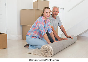 Happy couple rolling out new rug in their new home