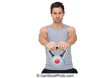 Portrait of a young man exercising with kettle bell