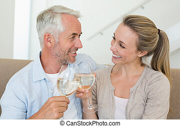 Happy couple sitting on couch toasting with white wine at...