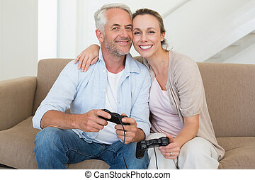 Happy couple having fun on the couch playing video games at...