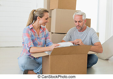 Happy couple unpacking cardboard moving boxes in their new...