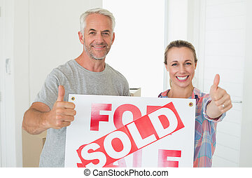 Happy couple standing and holding sold sign giving thumbs up...