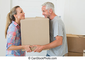 Happy couple carrying cardboard moving boxes