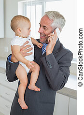 Smiling businessman holding his baby in the morning before...