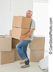 Smiling man carrying cardboard moving boxes in new home