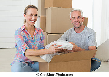 Happy couple unpacking cardboard moving boxes