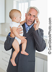 Distracted businessman holding his baby in the morning...