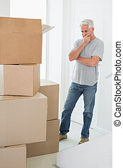 Thoughtful man looking at cardboard moving boxes in new home