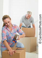 Happy couple sealing cardboard moving boxes in their old...