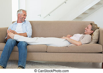 Caring man giving his partner a foot rub on the couch at...