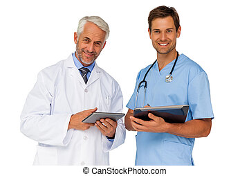 Portrait of male doctor and surgeon with digital tablets...