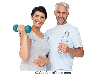 Happy fit couple with dumbbell and water bottle - Portrait...