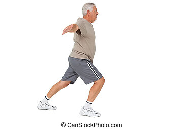 Full length side view of a senior man stretching hands over...