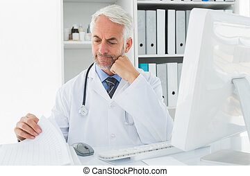 Mature male doctor with computer at