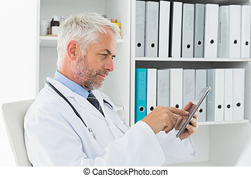 Concentrated doctor using digital tablet at medical office -...