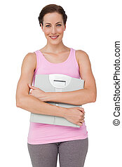 Portrait of a smiling young woman with weight scale